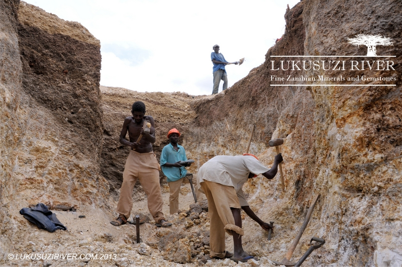 Mumba: The two workers in the front are the chisel men, who break the rock. The two men in the back are the dumpers, who shovel the loose material out of the pit and onto the dumps.